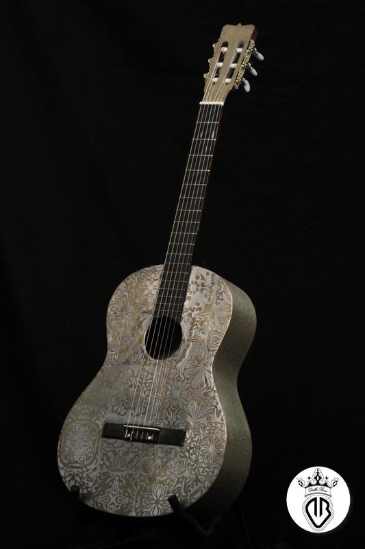 chitarra classica in legno con grafica a rilievo in acciaio e oro