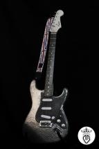 chitarra elettrica in legno con grafica a rilievo in acciaio